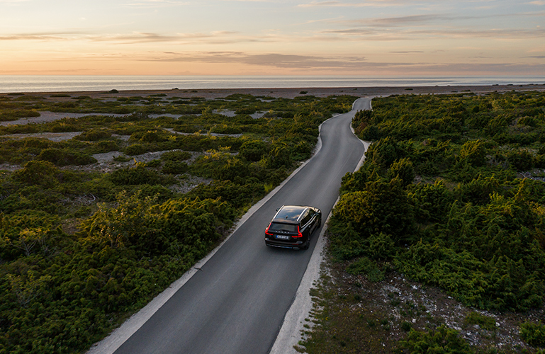 Volvo car driving along coastal road at sunset