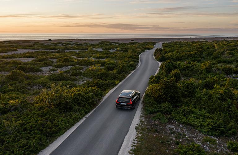 Volvobil som kör längs en kustväg i solnedgången