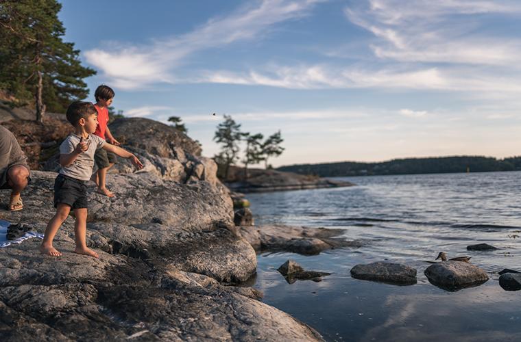 Två barn som matar ankor vid vattnet