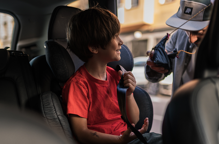Child smiling at father while sat inside Volvo car