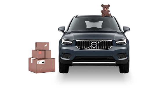 Teddybjörn ovanpå en Volvo bil bredvid flyttlådor