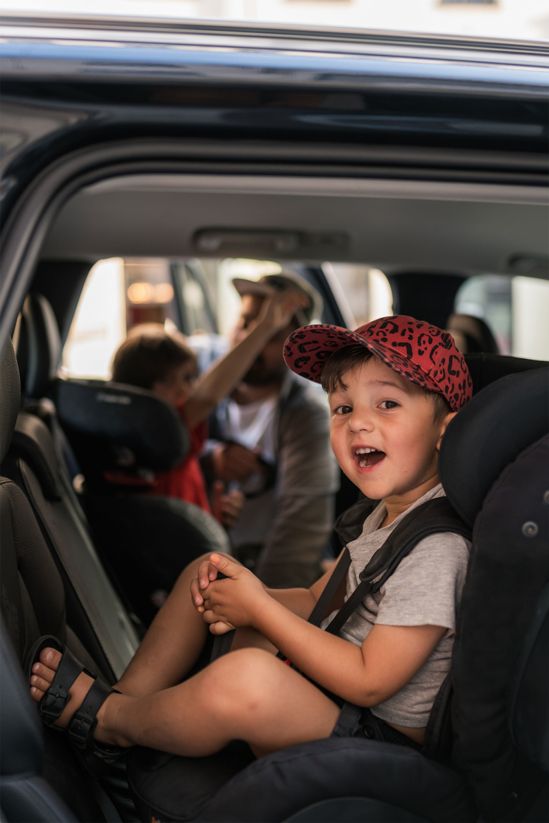 Young boy sat on child seat inside Volvo car