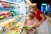 Mom and little boy buy fresh vegetable in grocery store
