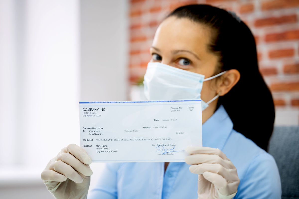 Woman In Face Mask Holding Paycheck