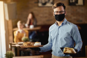 Young happy waiter wearing protective face mask while serving food