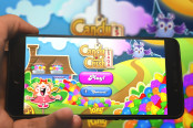 Hand holding phone with Candy Crash Saga logo