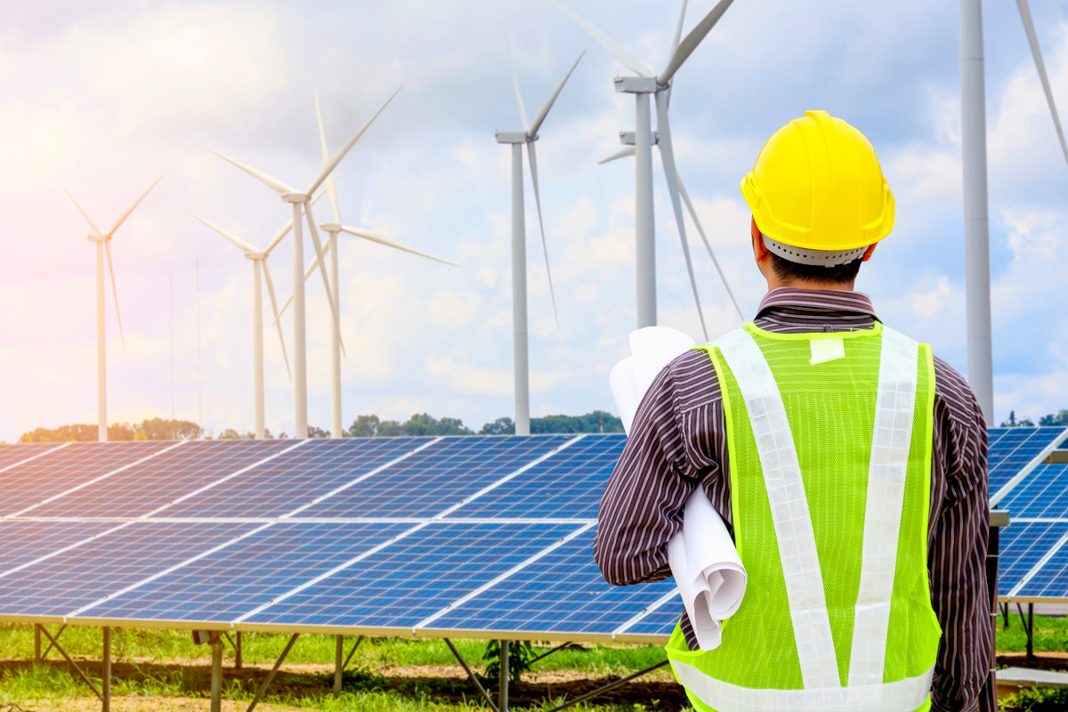 Young business man engineer with yellow helmet at solar panel and wind generators power plant construction