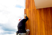 Men build siding Fiber Cement Board on wall exterior