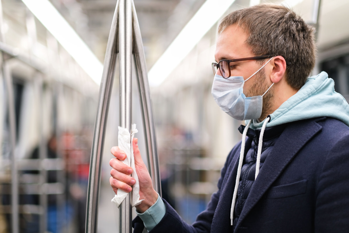 Close up of man holds a handrail in public transport