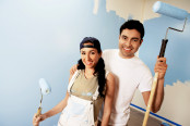 Portrait of smiling couple with paint rollers