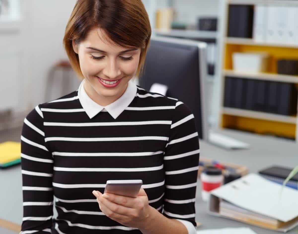Woman in black at white shirt smiling at phone