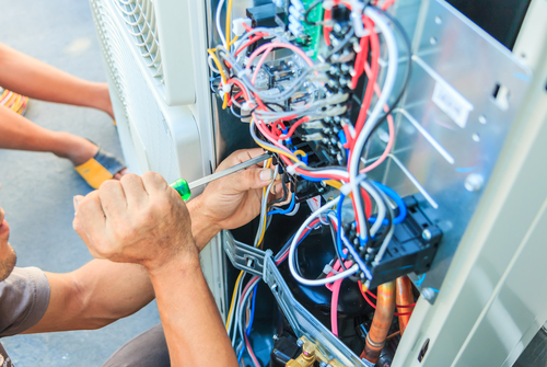 HVAC technician working on wires