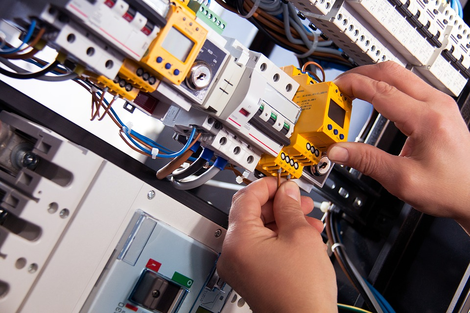 Electrician Working On A Circuit  Board With Yellow Circuit