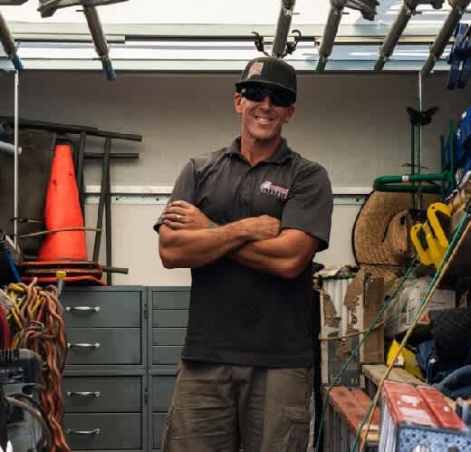 Electrician standing with a baseball hat and sun glasses