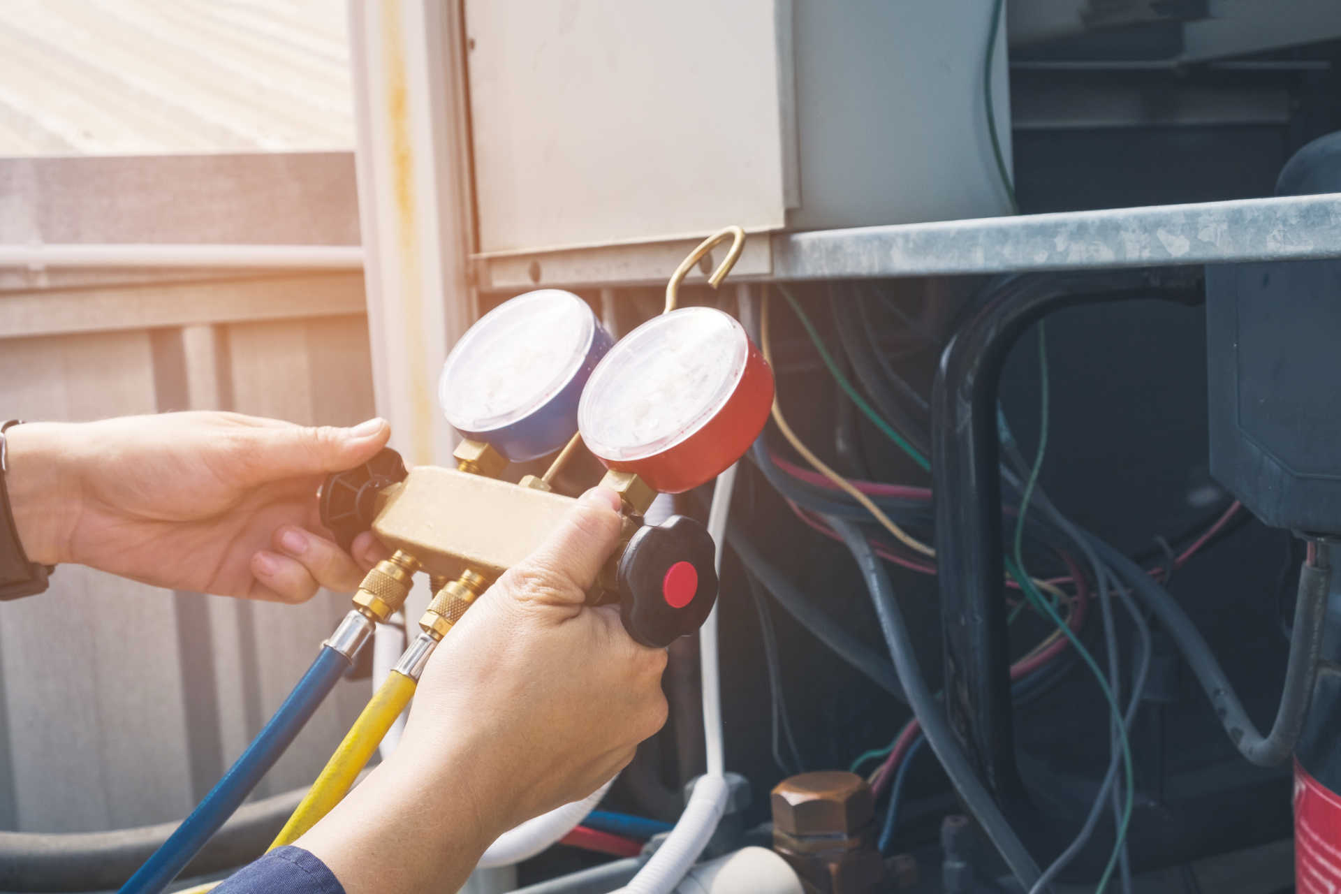 White hands holding red and blue HVAC gauges