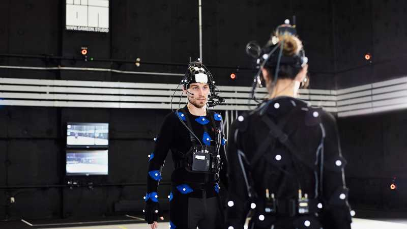 A man facing the camera talking to a woman. They are on a motion capture set doing a scene.  - Homepage / talent management