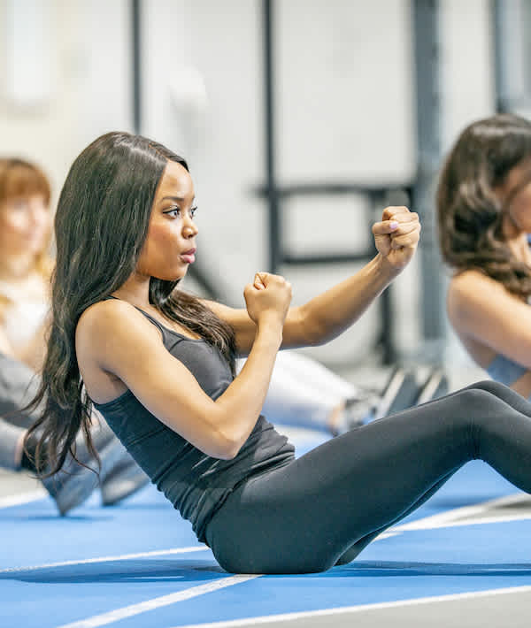 Ab Workout - A group of adults are indoors in a fitness center. They are sitting on the floor and doing abdominal exercises.