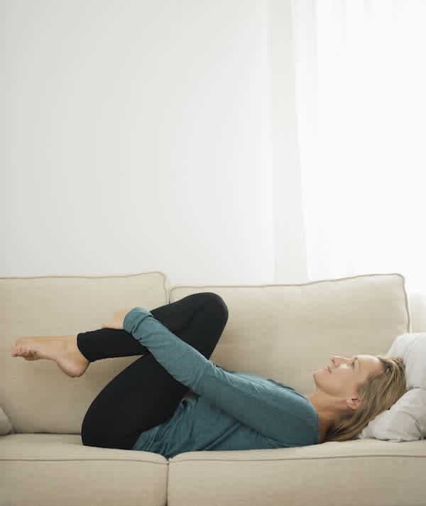 Mature woman lying on couch hugging knees