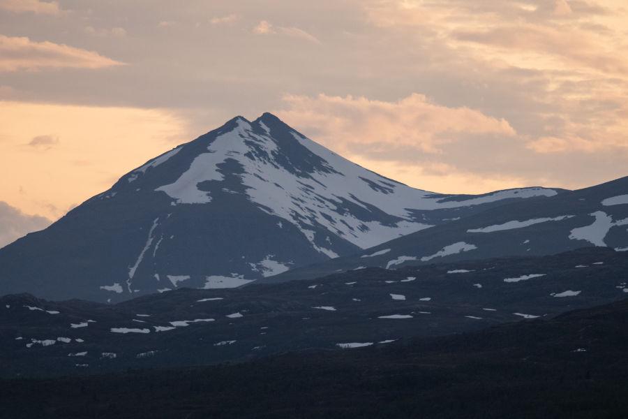 Luminen Norjan vuori ja oranssi pilvinen taivas