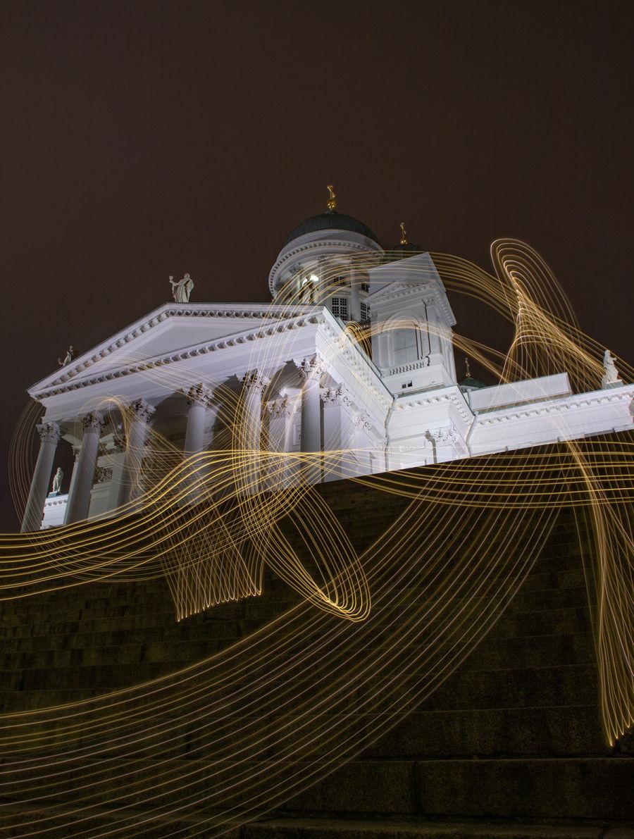 Valotikulla maalatut kellertävät valot pitkällä valotusajalla kuvatun Helsingin Tuomiokirkon edessä