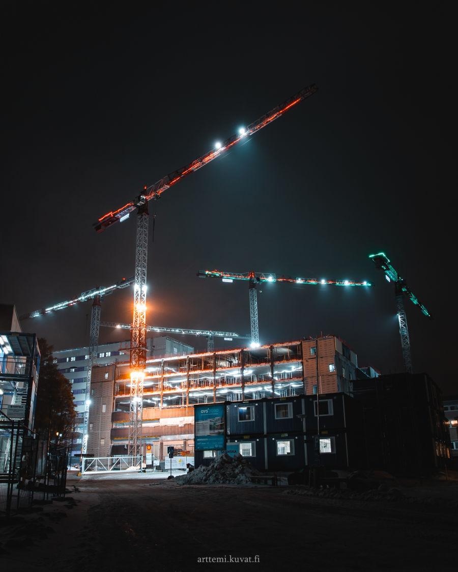 Yöllä olevia kesken rakentamisen olevia kerrostaloja, sekä nostokurkia.