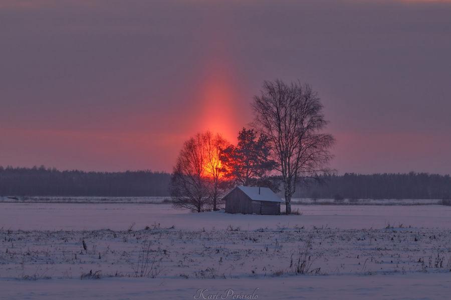Auringonlasku pellon päällä olevan puutalon ja sitä ympäröivän kolmen puun takana.