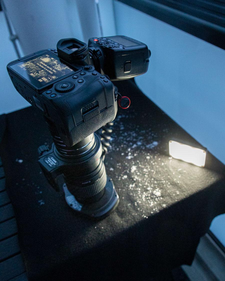 Kamera pitkällä makro-objektiivilla lumisen liinan päällä, sekä rengassalama.