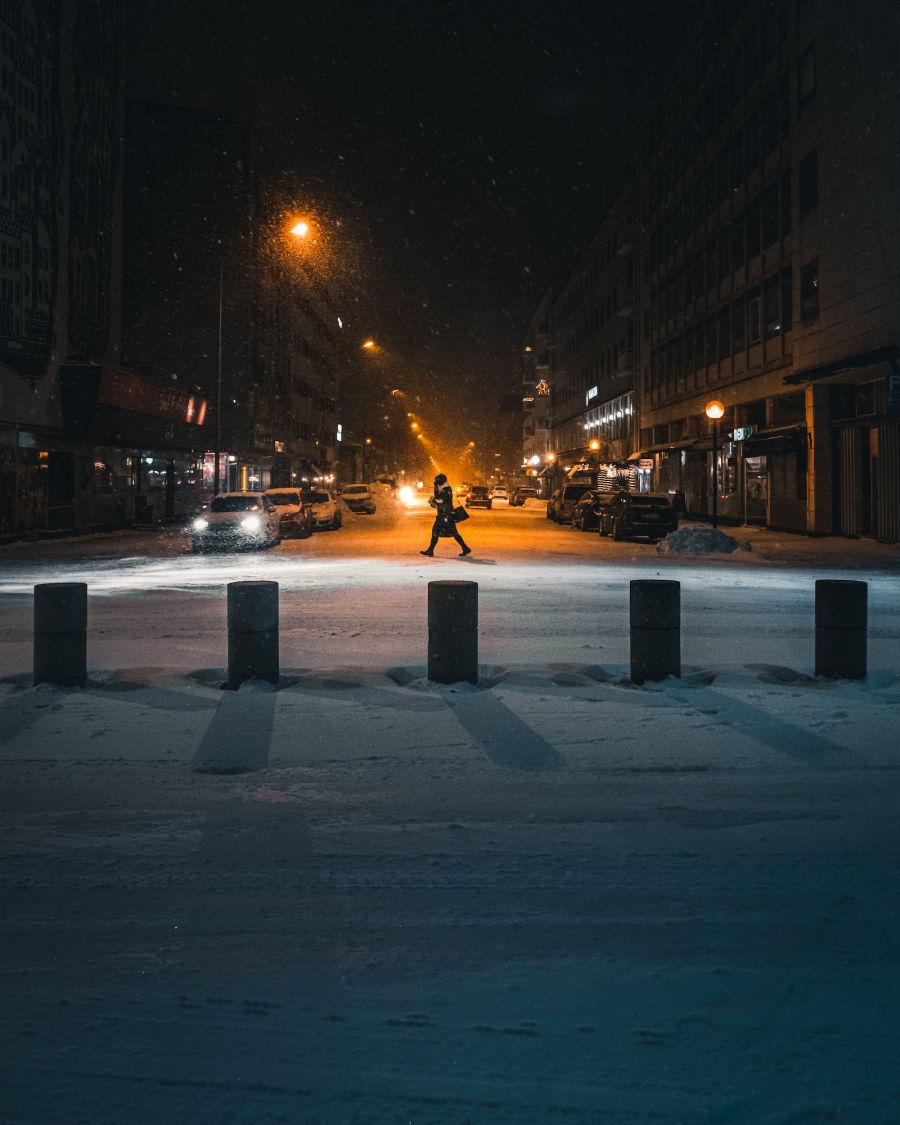 Nainen kävelee lumisateessa kaupungissa