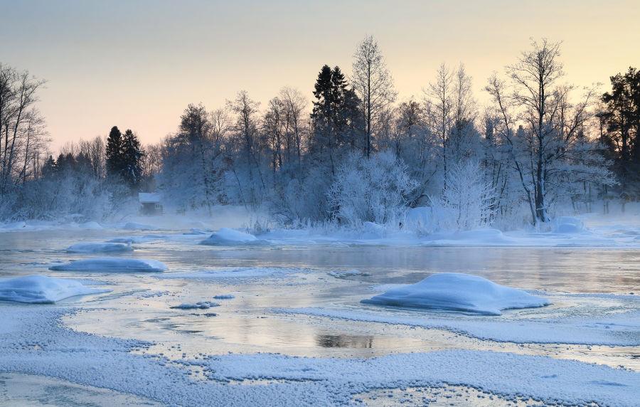 Osittain jäätynyt koski lumisen metsän ympäröivänä