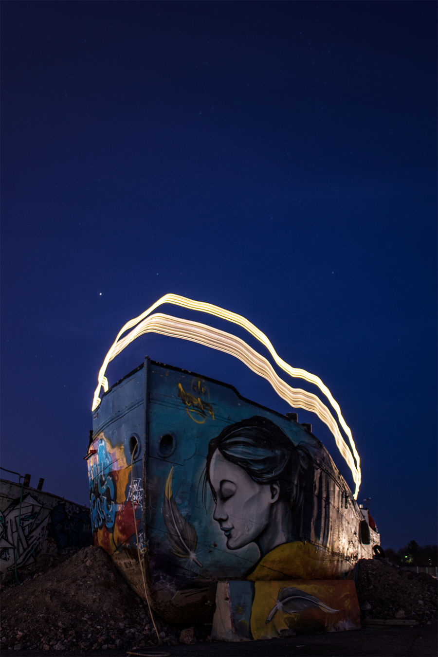 Graffiteilla täytetty laiva, jonka päällä on valolla maalattu kuvio pitkin laivan reunaa