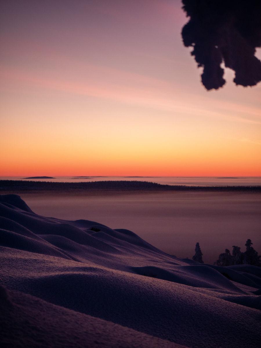 Auringonlasku usvaisella maisemalla lumisen mäen päältä