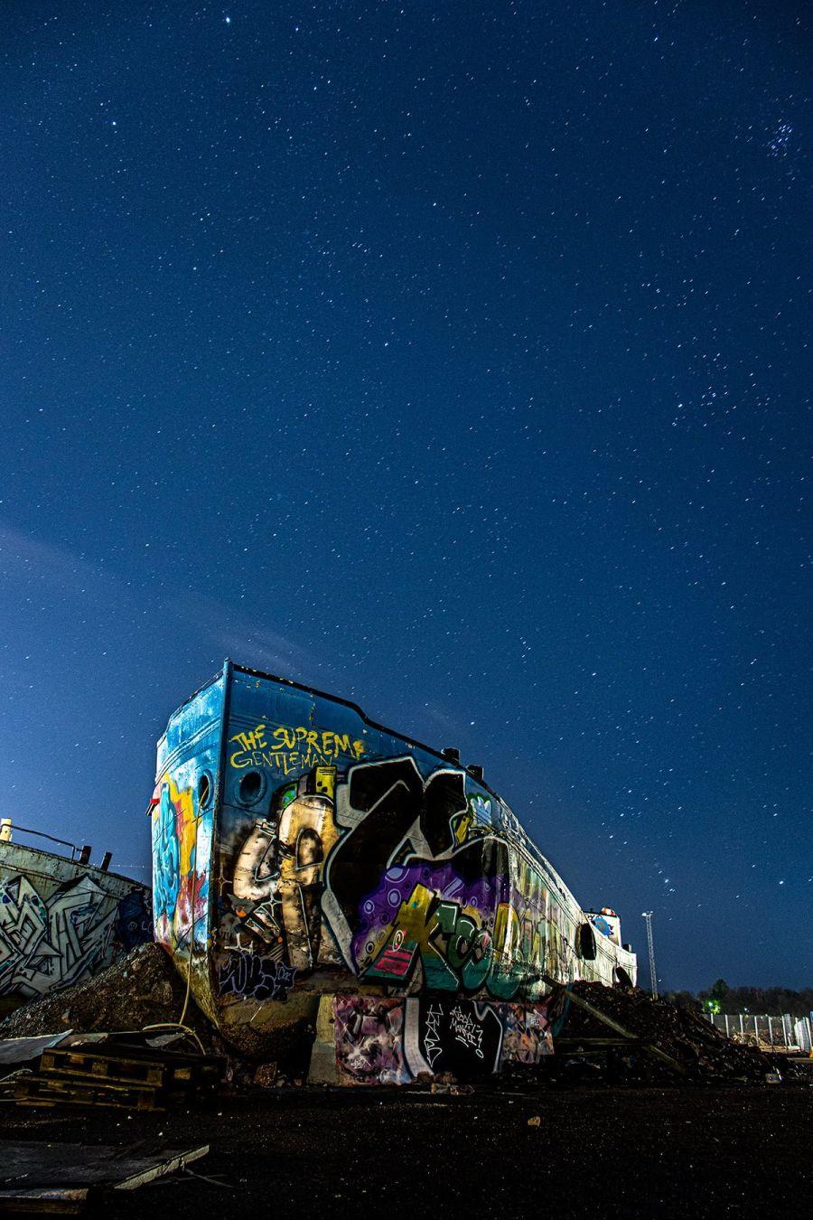 Hylätty vene täynnä graffiteja Helsingin Kalasatamassa, sekä tähdet taustalla