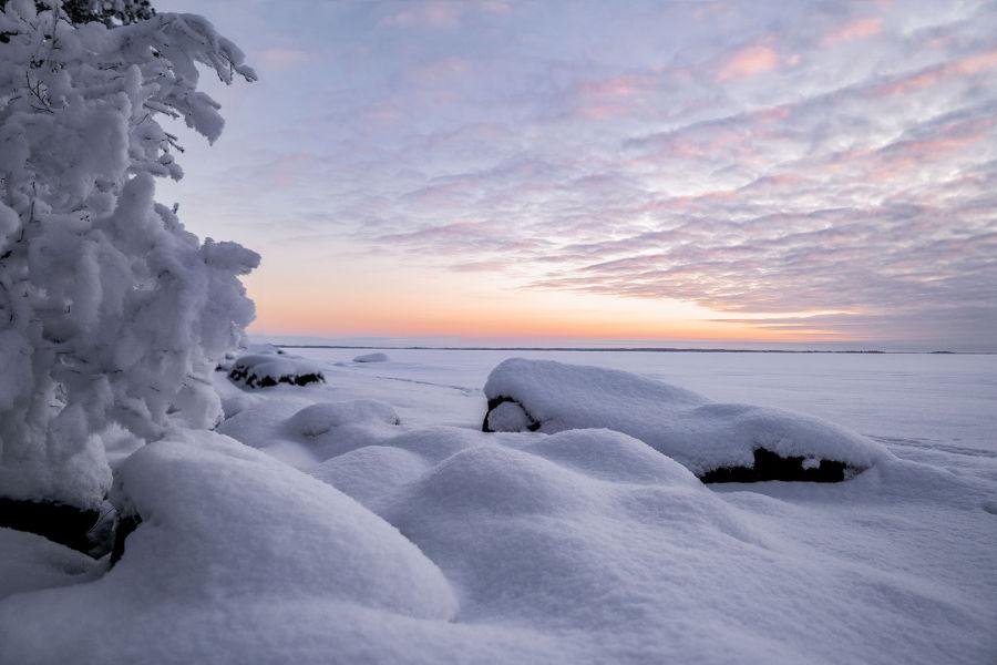 Luminen valoisa talvimaisema jäätyneen järven päällä