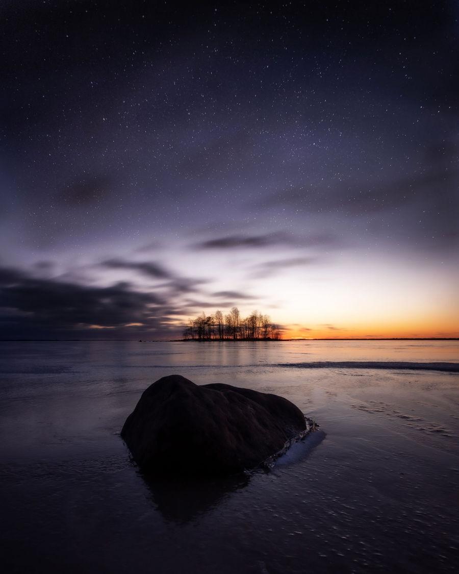 Kivi jäätyneen järven rannalla, taustalla näkyy saari, saaren päällä tähtitaivas