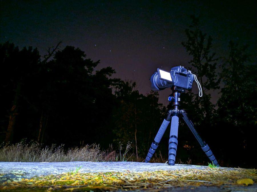 Kamera kolmijalalla kohti tähtitaivasta pimeässä metsässä