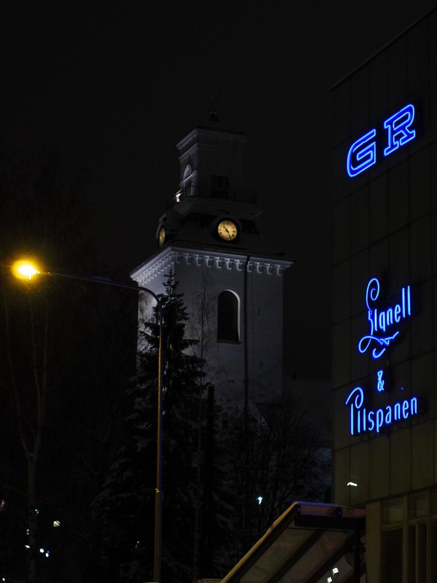 Kuopion kirkko pimeällä, vieressä on läheisen rakennuksen neon-kyltit.