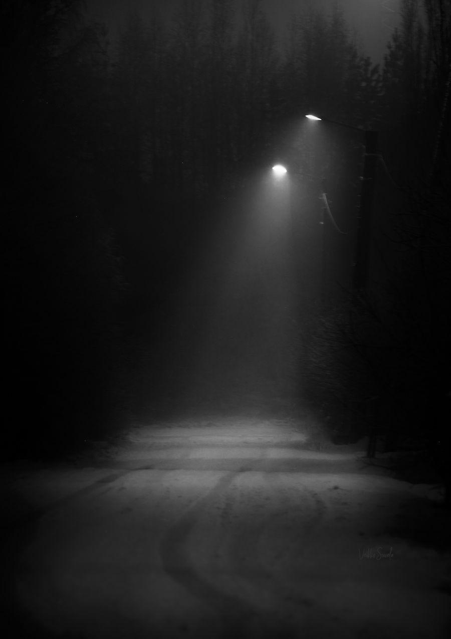 Pimeä katu yöllä lumisateessa, katuvalot valaisevat kadun.