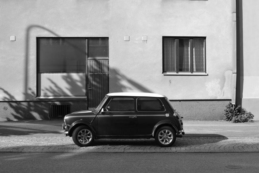 Mustavalkoinen kuva vanhanaikaisesta autosta kadun jalkakäytävällä