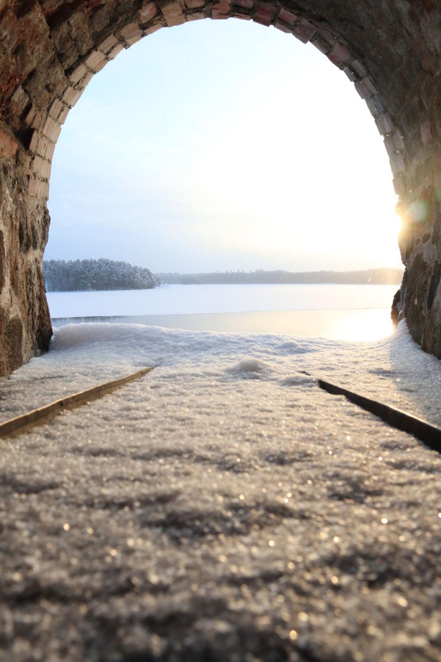 Aurinkoinen järvimaisema, jota ympäröi tiiliseinät
