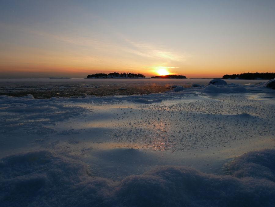 Auringonlasku jäätyneen meren päällä
