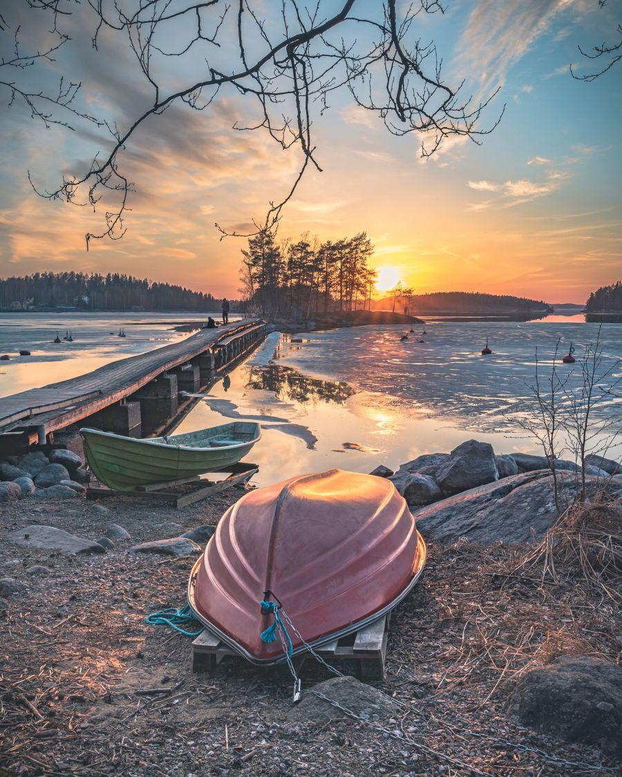 Soutuvene järven rannalla auringonlaskussa