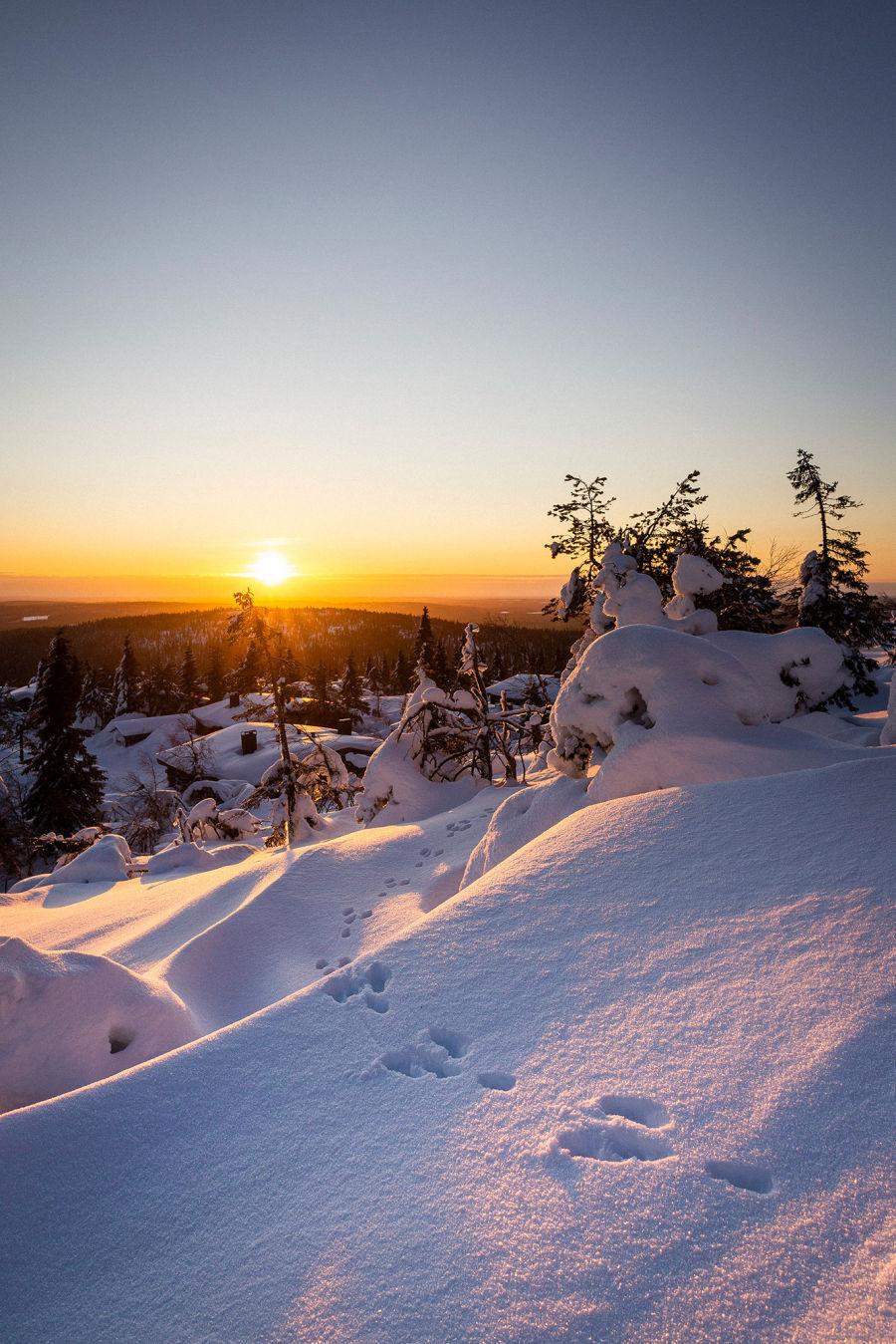 Luminen maisema mäen päältä kohti auringonlaskua