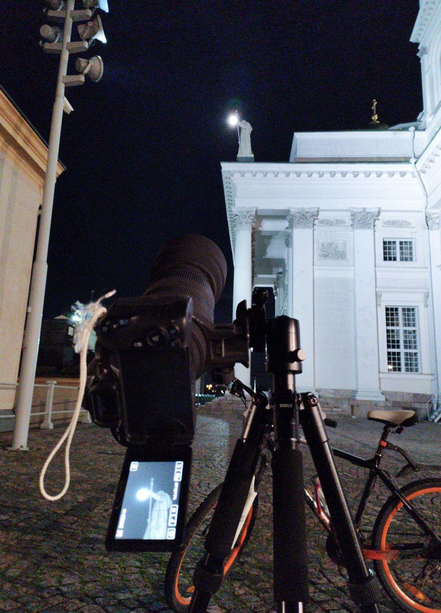 Kamera ottamassa kuvaa teleobjektiivilla kirkon patsaasta, kameran takana näkyy Tuomiokirkko