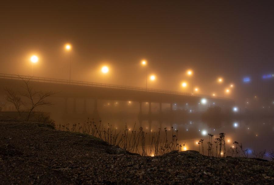 Sumuinen silta, jota valaisevat katuvalot sumun peitossa.
