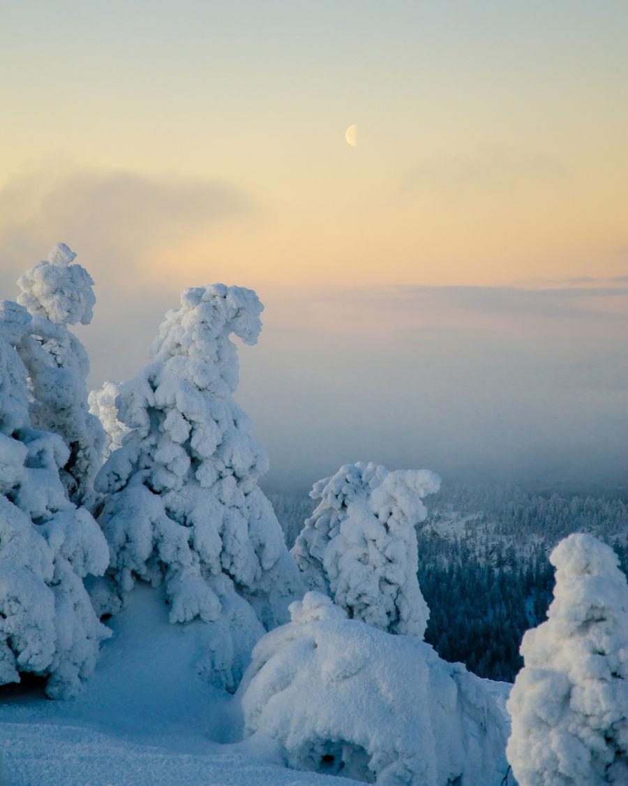 Usvan peittämä talvimaisema kuvattuna korkealta mäeltä, oranssin taivaan keskellä näkyy kuu