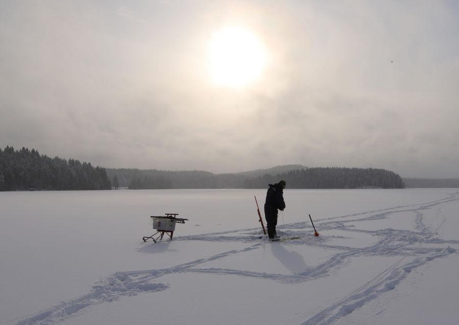 Kalastaja lumen peittämän järven päällä auringon paistaessa taivaalla pilvien takana