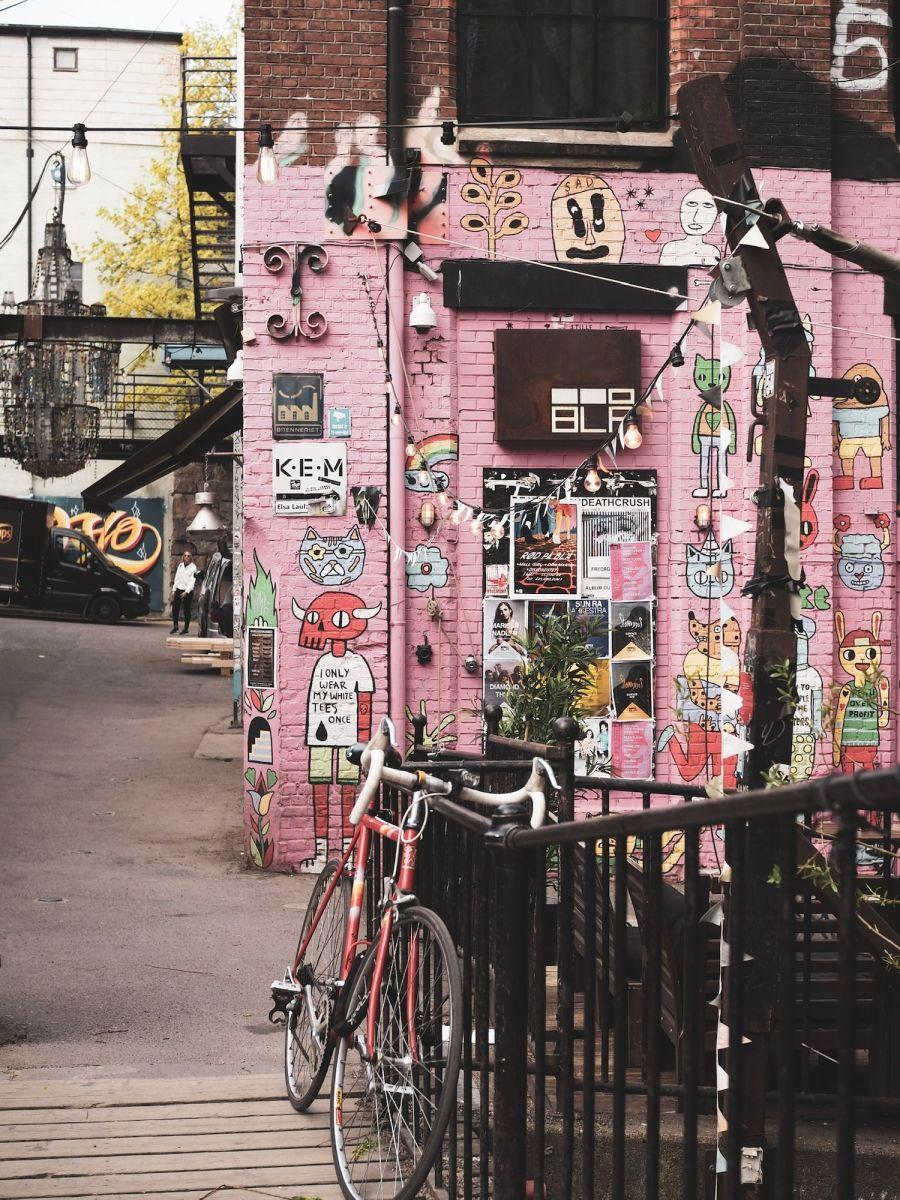 Kuva pinkistä seinästä, joka on täytetty julisteilla, sekä sen edessä olevasta polkupyörästä.