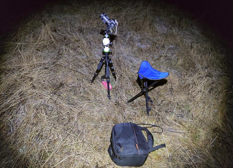 Kamera kolmijalalla, kasattava tuoli ja kamerareppu yöllä pellolla taskulampun valossa