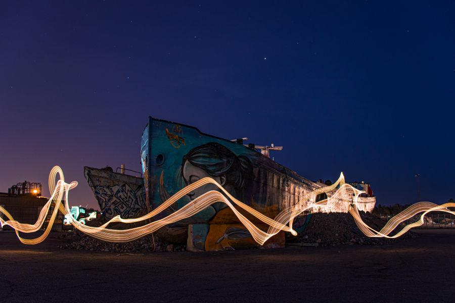 Valolla maalattu pitkän valoituksen kuvio hylätyn graffiteilla täytetyn laivan edessä yöllä