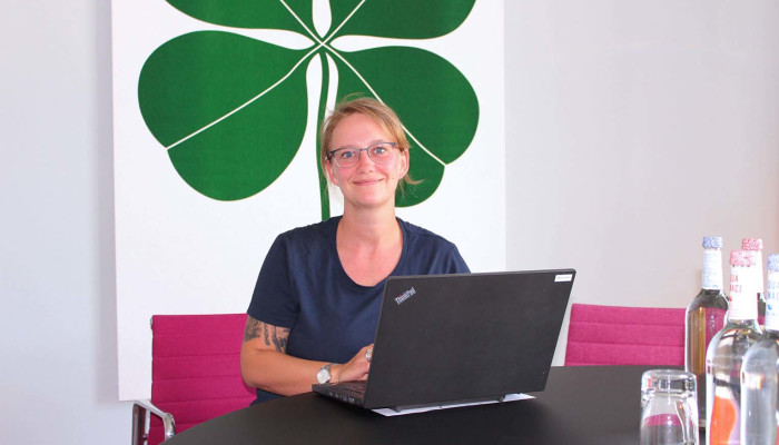 Operations Coordinator Laura am Standort Heidelberg Colours am Laptop